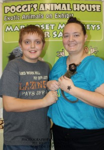 Mother and son holding a Marmoset Monkey